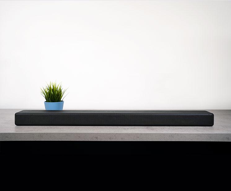 Abbildung zeigt die Soiny Soundbar HT G700 auf einem Tisch mit einer Pflanze